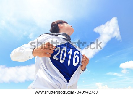 Business man pulling his t-shirt open, showing 2016 text with a superhero suit underneath his suit - stock photo