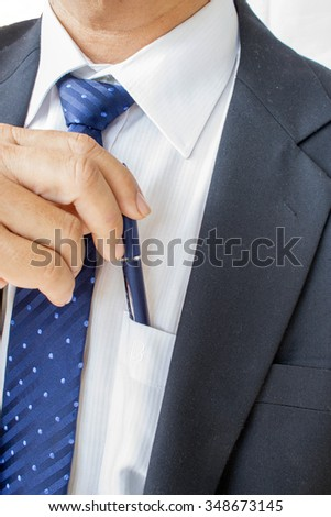 business man pulling or putting blue pen in his pocket - stock photo