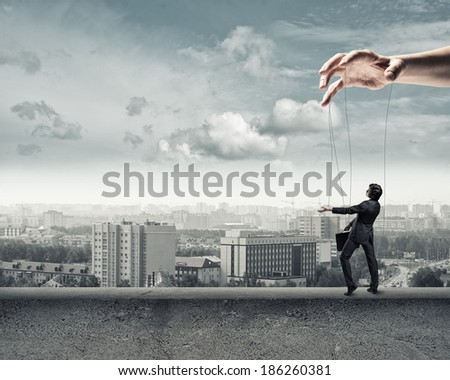 business man puppet walks on the concrete parapet - stock photo