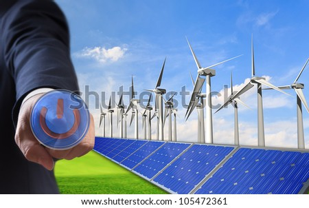 business man push power button,  Panels with solar cells and wind generators on a green field with blue sky - stock photo