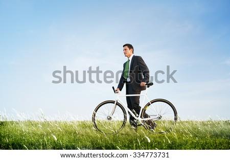 Business Man Pushing Bike Outdoors Concept - stock photo