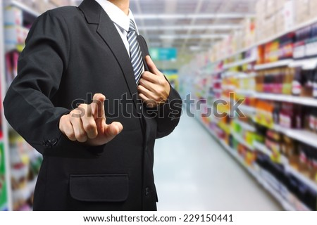 Business Man pushing on a touch screen interface in supermarket in blurry   - stock photo