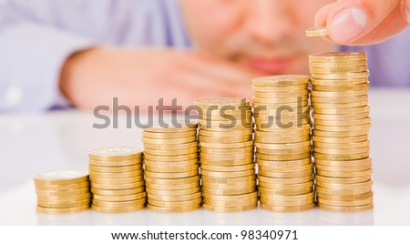 Business man put coins to money staircase - stock photo