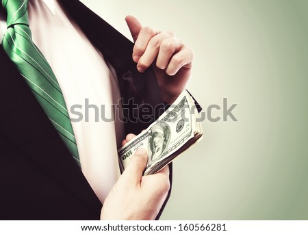 Business Man putting  a wad of cash in his suit jacket pocket on green vintage background - stock photo