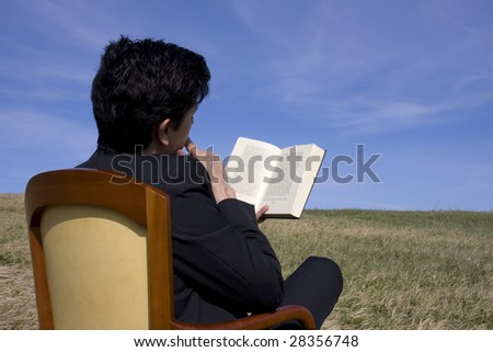 Business man reading a book on the meadow (text book with intentional blur) - stock photo