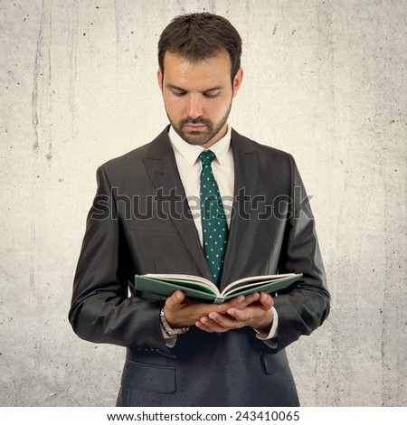 Business man reading a book over isolated background  - stock photo