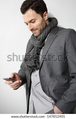 Business man reading a interesting message on his cell phone, isolated on gray