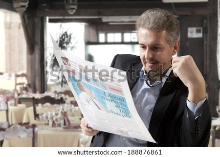 Business man reading a newspaper, cafe backgrounds - stock photo