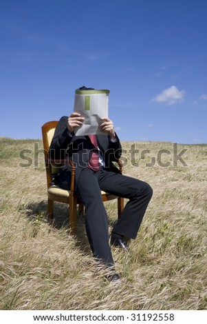 Business man reading a newspaper on the nature - stock photo