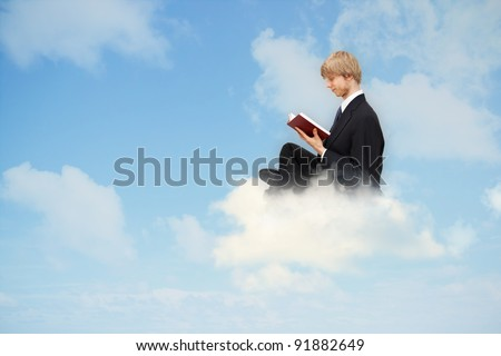 Business man reading book on the cloud - stock photo