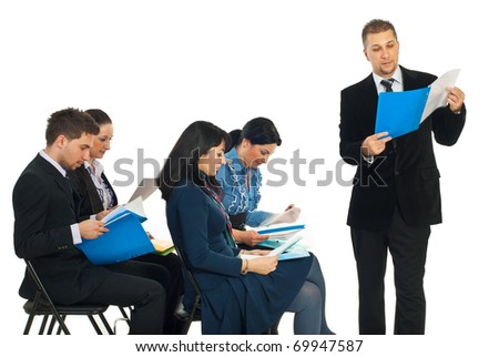 Business man reading from a folder at seminar and his colleagues business people checking their folders over white background - stock photo