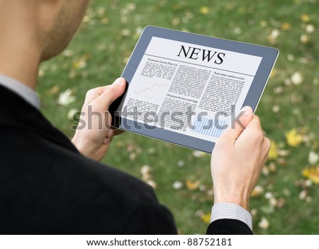 Business man reading news on digital tablet at park. - stock photo