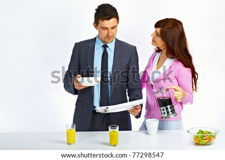 Business man reading newspaper in the kitchen before go to work and his wife holding kettle with coffee near him - stock photo