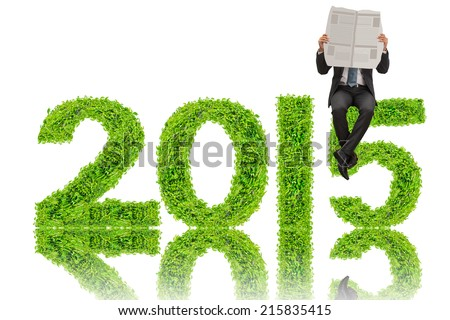 business man reading newspaper on 2015 year made from green plant - stock photo