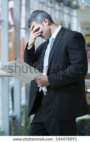 Business man reads document and covers face