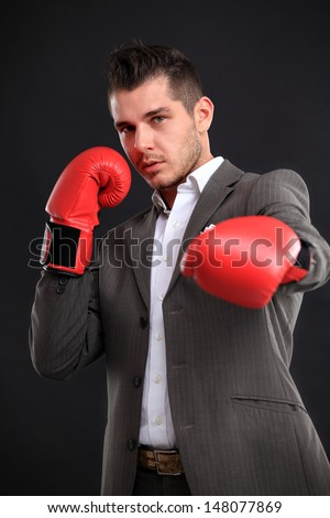 Business man ready to fight with boxing gloves - isolated over black background