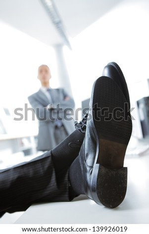 Business man relaxing at work. In the background is angry boss - stock photo