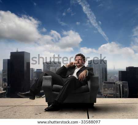 business man relaxing on armchair against a cityscape