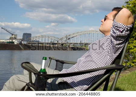 Business man relaxing on the riverside