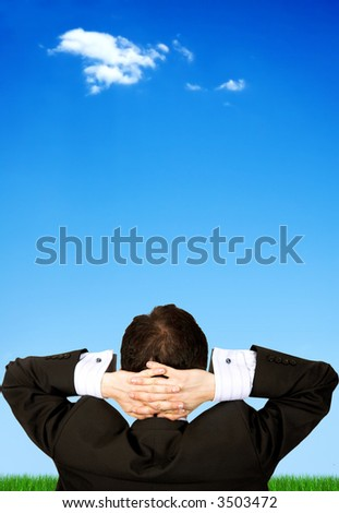 business man relaxing outdoors in front of a beautiful blue sky