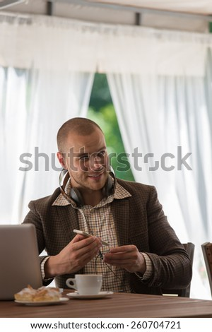 Business man resting at cafe and listening music using vintage headphones