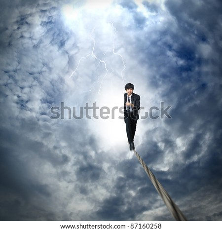 Business man run on the rope high in the sky - stock photo