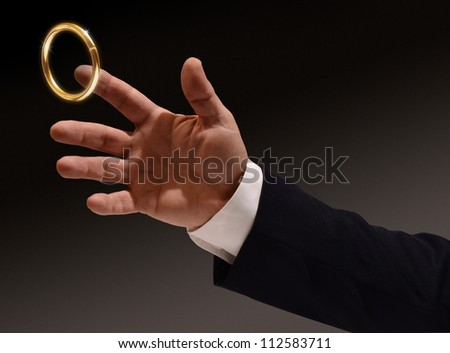 Business man's hand reaching for the brass ring - stock photo