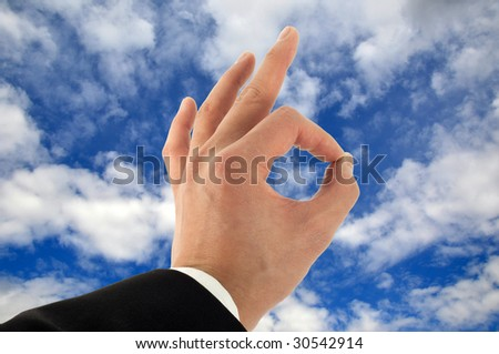 Business man's hand signing okay in the sky - stock photo