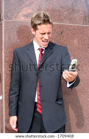 Business man screaming into cell phone - stock photo
