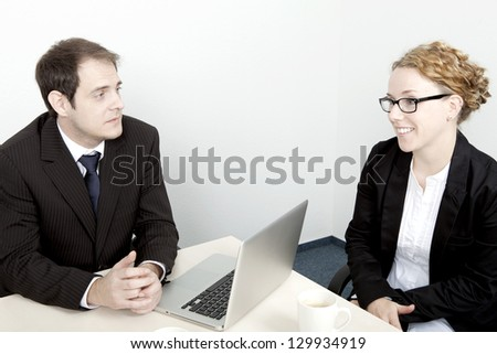 Business man seated at his desk conducting an interview with an attractive female job applicant wearing glasses who is smiling at him while answering his questions
