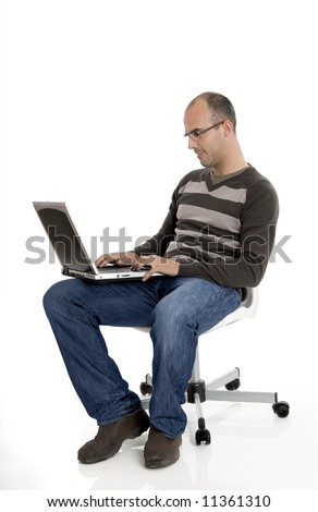 Business man seated on chair and working on a laptop - stock photo