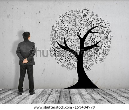 Business man see concept picture of idea tree on White Brick floor and Concrete wall  - stock photo
