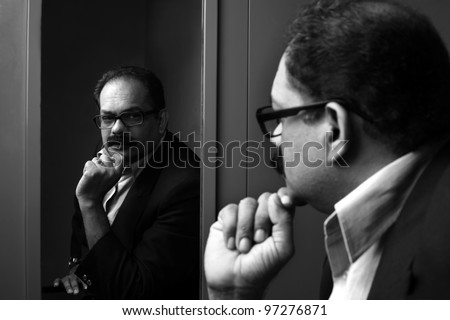 Business man seeing his reflection in the mirror