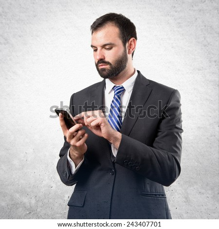 Business man sending a message over textured background.
