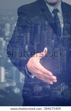 business man shaking hands and city scape double exposure,business,cool tone - stock photo