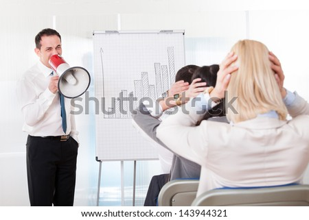 Business Man Shouting In Megaphone Indoors In Office - stock photo