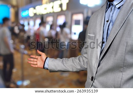 Business Man show welcome or invite gesture on Movie Ticket System Background as Entertainment business or Theatre cinema complex concept. - stock photo