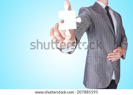business man showing blank jigsaw puzzle piece with concept for business strength and success  - stock photo