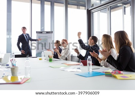 Business man showing ground-plan during meeting in modern office while his colleagues cheering. - stock photo