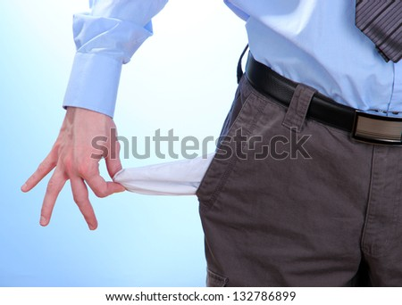 Business man showing his empty pocket, on blue background