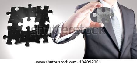 "Business man showing missing metal jigsaw puzzle piece with ""SUCCESS"" wording. Concept for business strength and success. - stock photo"