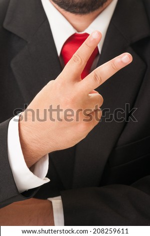 Business man showing number two or peace sign using his fingers