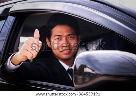 Business man showing sit and smiling in car.
