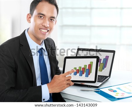 Business man showing tablet pc with success growth graph on screen - stock photo