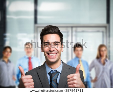 Business man showing thumbs up in front of his team - stock photo