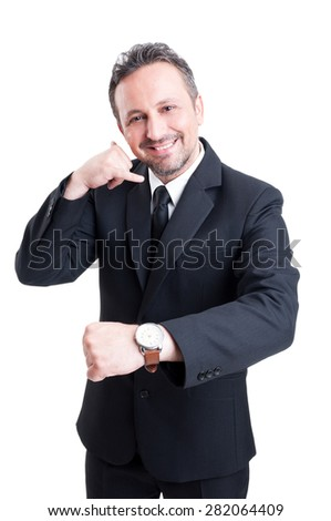 Business man showing watch and making call me gesture with hand