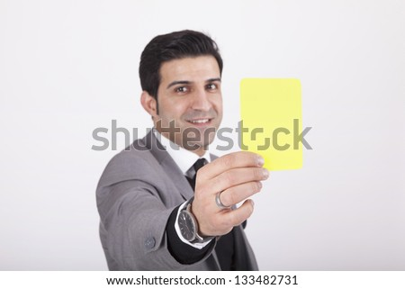 business man showing yellow card as as symbol for warning and/or negative expression.