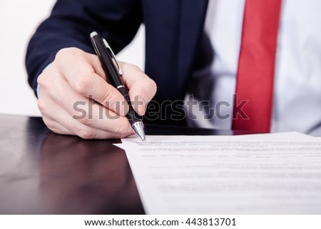 Business man signing a contract. A hand holding a fountain pen and about to sign a letter. Styling and small amount of grain applied. - stock photo