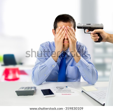 business man signing a piece of paper with someone pointing a gun at his head - stock photo