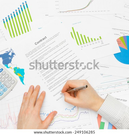 Business man signing contract with silver pen - stock photo